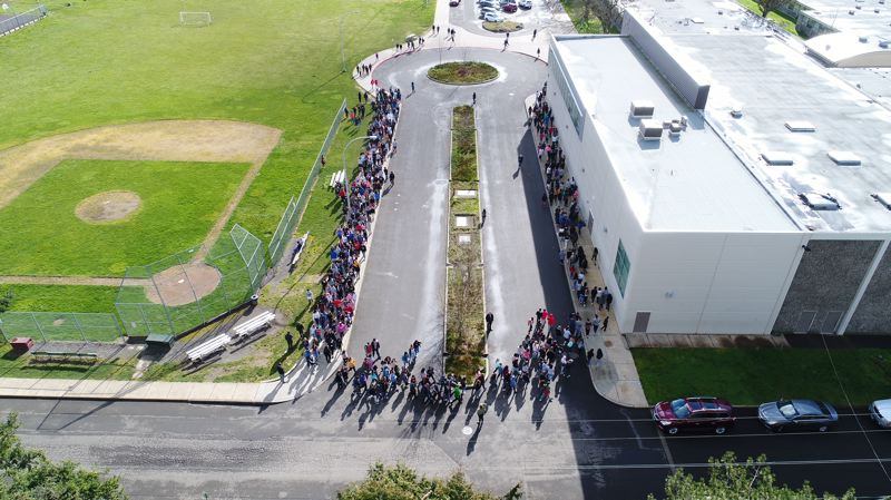 PAMPLIN MEDIA GROUP: ALVARO FONTAN - In Milwaukie, Rowe Middle School students marched around the turn-around area for school buses during their walkout event on March 14, to protest Congress' inaction on preventing gun violence in schools.