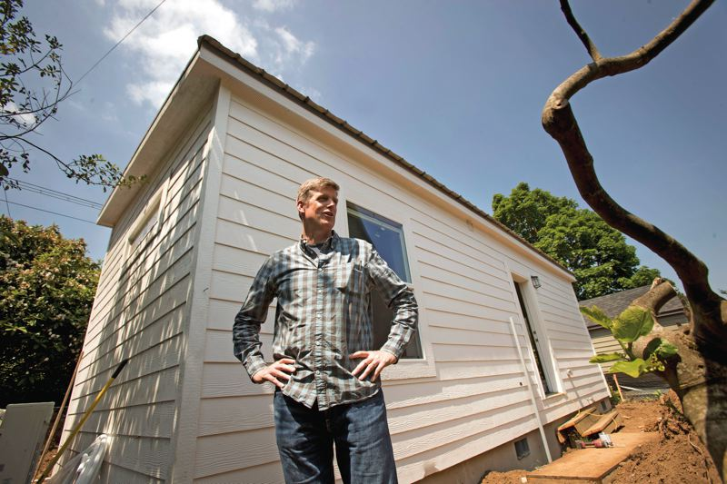 TRIBUNE PHOTO: JAIME VALDEZ - Patrick Quinton, former director of the Portland Development Commission, is running a new company, Dweller, that puts pre-fab accessory dwelling units in peoples yards. Property owners can buy the ADUs for $125,000. Or Dweller will operate them as rentals, sharing 30 percent of the rent; eventually the homeowner owns the unit outright. Here Quinton stands next to his second ADU near Northeast Alberta Street.