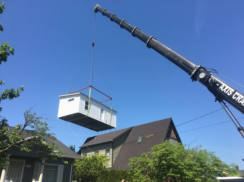 COURTESY PHOTO: DWELLER - A massive crane lifts a pre-fabricated ADU over the main house to place it on a foundation laid in the rear yard. Dweller figures perhaps half its Portland units will require a crane, so the costs are built into its fixed price.