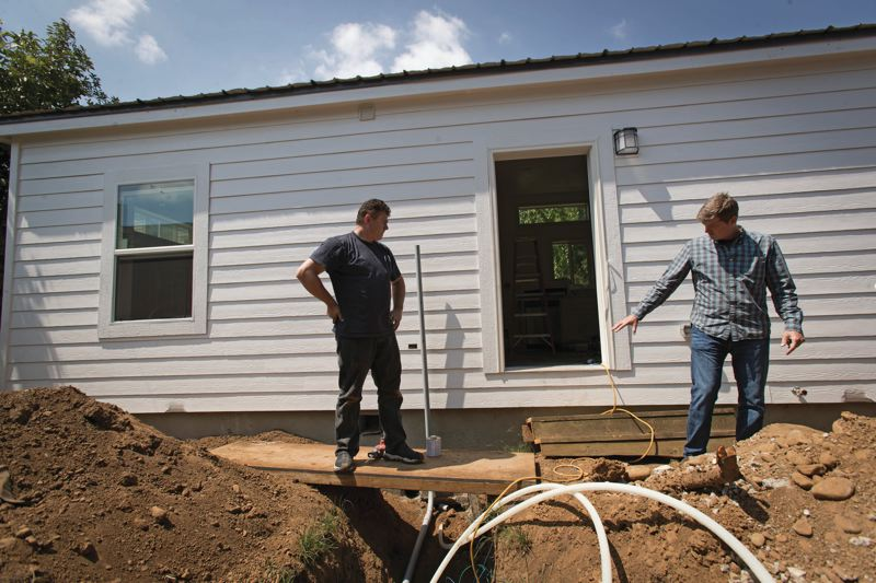 TRIBUNE PHOTO: JAIME VALDEZ - Quinton, right, talks with an electrician who is connecting the ADU to power after it was placed on a foundation in a clients yard near Northeast Alberta Street.