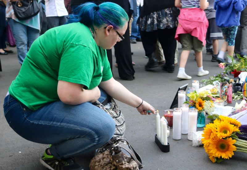 VALLEY TIMES PHOTO: ZANE SPARLING - A woman lights a candle at a memorial for chef Daniel Brophy on Monday, June 4 in downtown Portland.