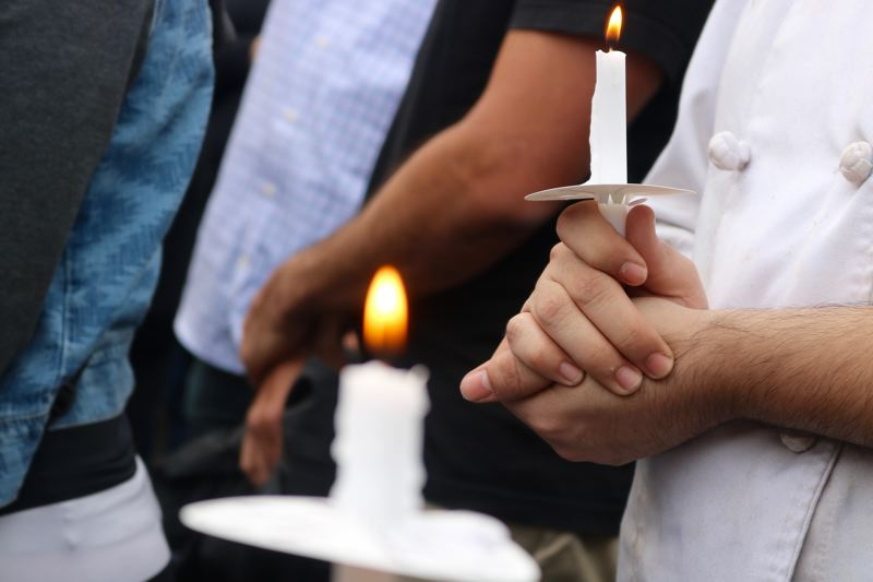VALLEY TIMES PHOTO: ZANE SPARLING - Mourners hold candles during a vigil for chef Daniel Brophy on Monday, June 4 at the Oregon Culinary Institute in downtown Portland.