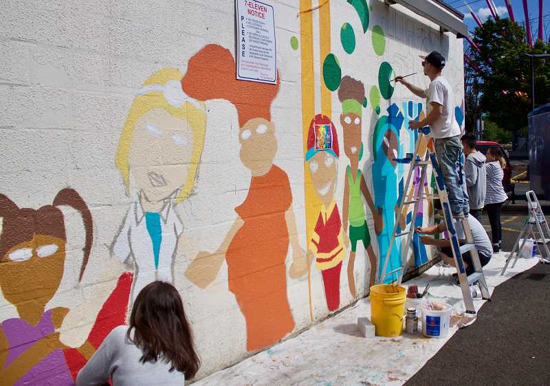 OUTLOOK PHOTO: CHRISTOPHER KEIZUR - Members of Greshams Youth Advisory Council paint a new mural in Rockwood that will help reduce crime and remember a teenager who was killed after a hate crime.