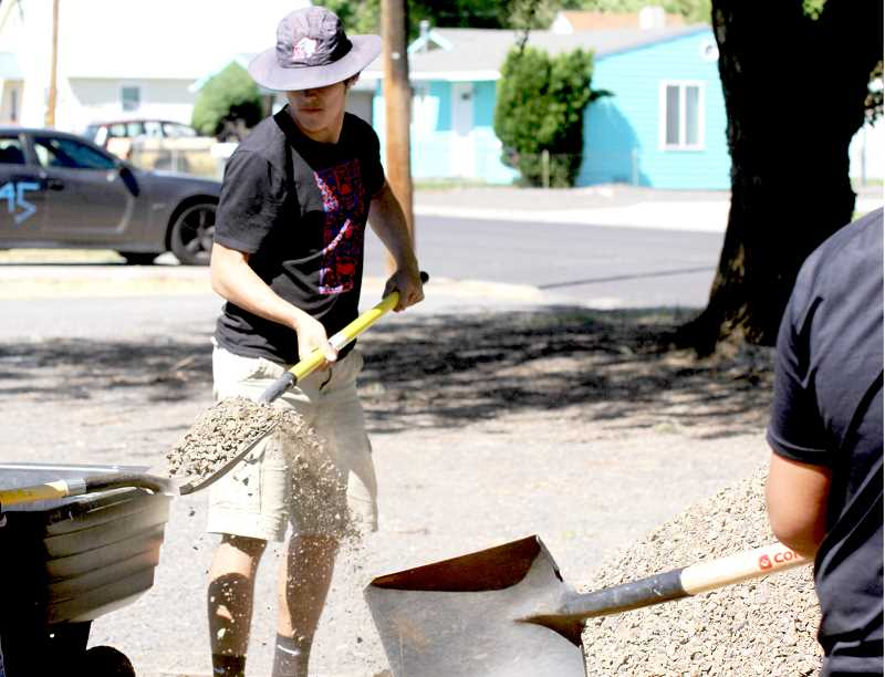 STEELE HAUGEN - Madras football player Keenan Miller shovels gravel at the MGM community center as part of a service project.
