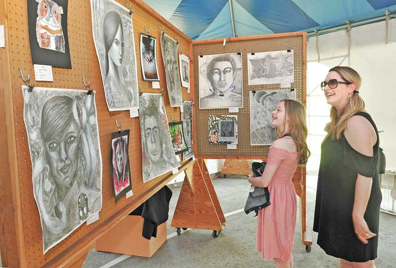 SPOKESMAN PHOTOS: VERN UYETAKE - Michelle Jakosen and her daughter Alina take in the student art show at Wilsonville Festival of the Arts.