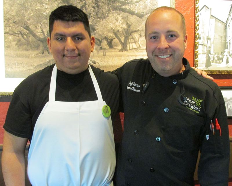 OUTLOOK PHOTOS: TERESA CARSON - Carlos is pictured with his boss, Jeff Watson, general manager of the Gresham Olive Garden. Olive Garden gives these students job expereince by having them clean menus, vacuum and engage in other chores.