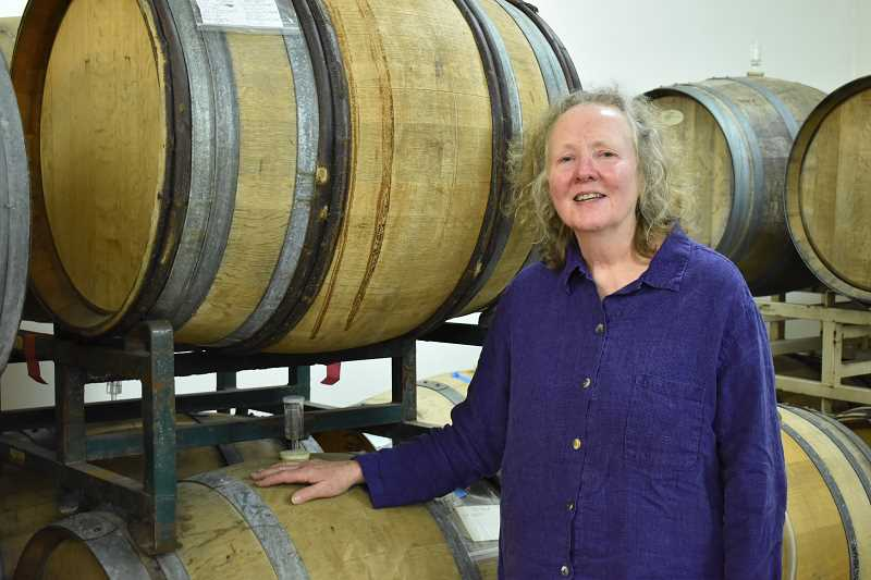 ESTACADA NEWS PHOTO: EMILY LINDSTRAND - Jan Wallinder of Forest Edge Vineyard stands next to the operations barrels of wine. Typically, the wine ages for at least several years.