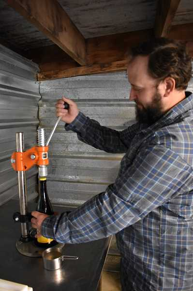 ESTACADA NEWS PHOTO: EMILY LINDSTRAND - Dan Lawrence of Stone Circle Cider bottles his product. The cider is inspired by the English tradition.