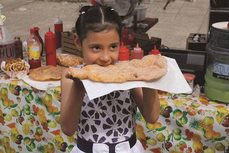 LINDSAY KEEFER - Abigail Trapala, 7, of Woodburn, bites into an elephant ear served by El Mercadito, one of many vendors at Taste of Woodburn in downtown Woodburn over the weekend.