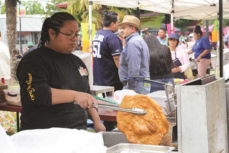LINDSAY KEEFER - Carmen Morales, of El Mercadito, fries an elephant ear at Taste of Woodburn over the weekend.