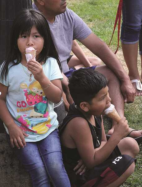 LINDSAY KEEFER - Siblings Ana Elvia and Carlos Marcelo, of Gresham, enjoy ice cream cones while listening to live music at Taste of Woodburn on Sunday.