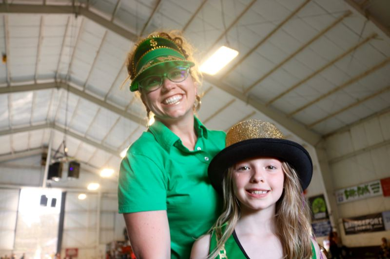TRIBUNE PHOTO: ZANE SPARLING - Tigris Mackelprang and her mom, Lisa Born, wear green and gold in support of the High Rollers.