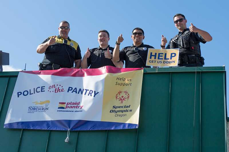 STAFF PHOTO: CHRISTOPHER OERTELL - Hillsboro police officers and cadets raise money on the roof of the Plaid Pantry on TV Highway looking for donations for Special Olympics in Hillsboro.