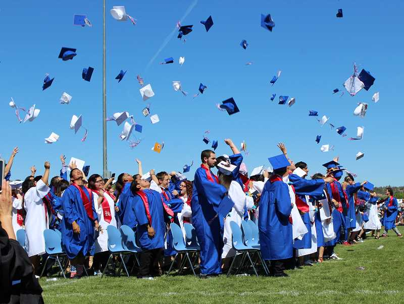 HOLLY M. GILL/MADRAS PIONEER - MHS grads toss their hats in the air at the conclusion of the morning graduation on June 2.