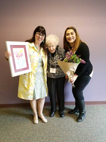 SUBMITTED PHOTO: LISA OETKEN - Schwartz (left) and Lambert (right) pose for a photo with The Springs resident Norma Jennings who won an award for her painting of a bouqet through the Alzheimers Associations Memories in the Making art program.