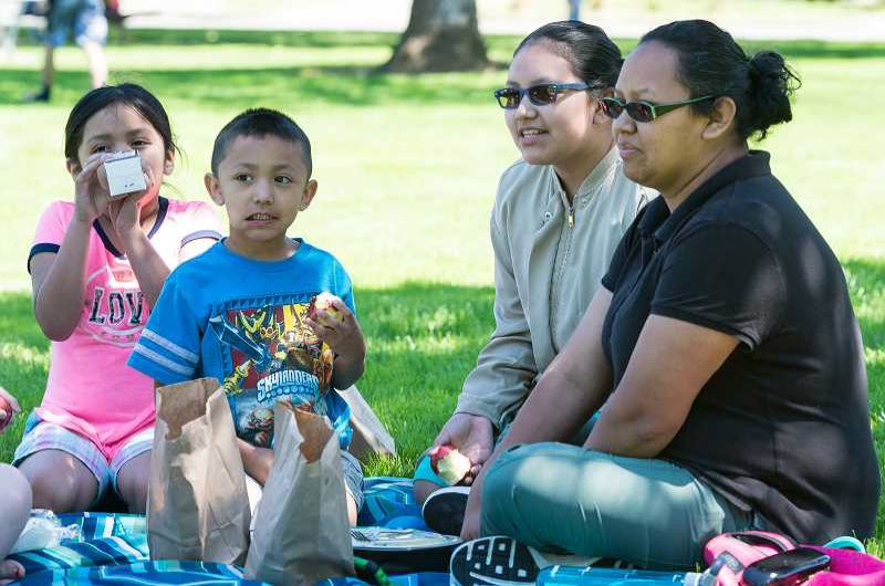 STAFF PHOTO: CHRISTOPHER OERTELL - A family enjoys summer lunch in Forest Grove last year. The summer lunch program is open to babies, children and teens up to age 18.