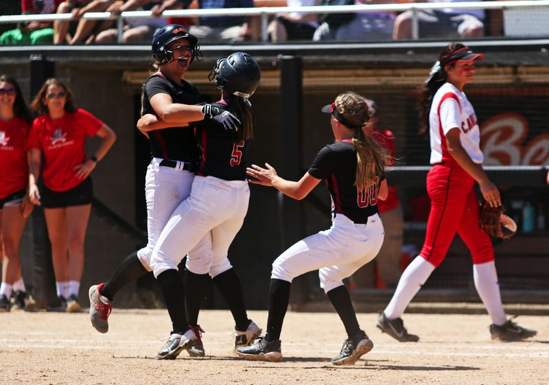 TIMES PHOTO: DAN BROOD - Tualatin High School freshman Taylor Corcoran (left) is greeted by seniors Zoe Olivera (5) and Kayla Laird following her game-winning single during Saturdays Class 6A state championship game.