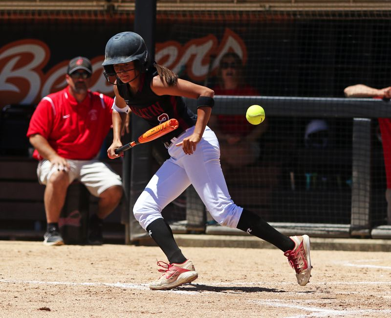 TIMES PHOTO: DAN BROOD - Tualatin sophomore Tia Ridings puts down a bunt single during the third inning of Saturdays state title tile. Ridings scored the Wolves first run in their 4-3 victory over Clackamas.