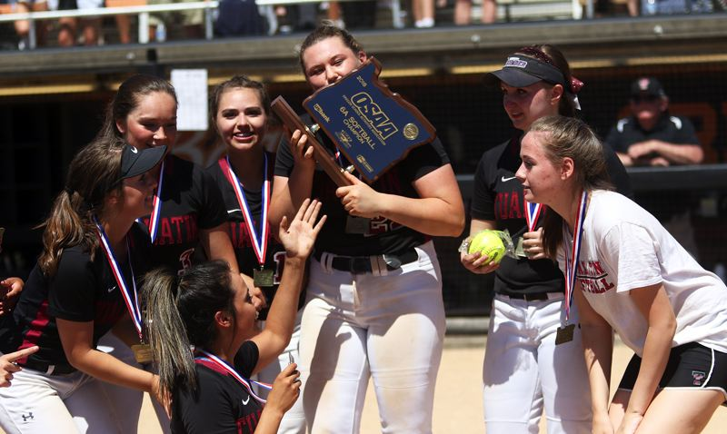 TIMES PHOTO: DAN BROOD - Members of the Tualatin High School softball team celebrate with the championship trophy following the 4-3 win over Clackamas on Saturday.