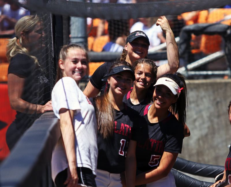 TIMES PHOTO: DAN BROOD - Members of the Tualatin High School softball team, including Elizabeth Hillier, Andrea Gomez, Emily Johansen, Tia Ridings and Zoe Olivera smile in the dugout prior to the state championship gmae on Saturday.