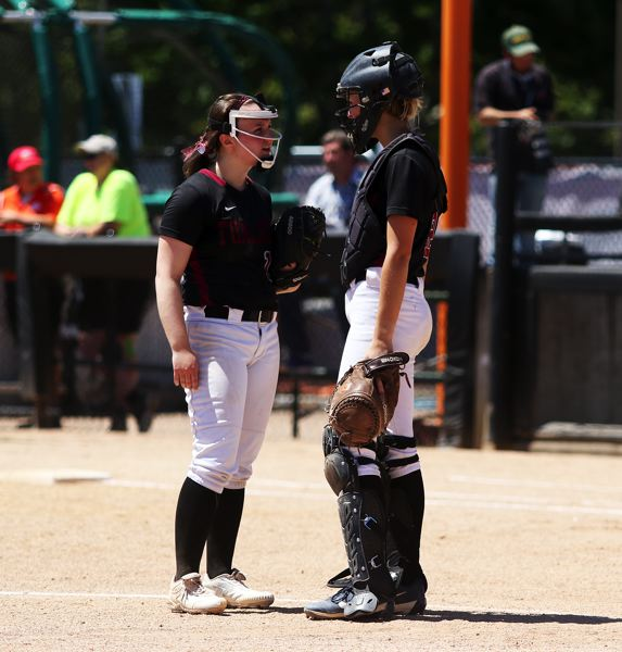 TIMES PHOTO: DAN BROOD - Tualatin seniors Megan Woodward (left) and Ella Hillier have a discussion in the pitcher's circle.