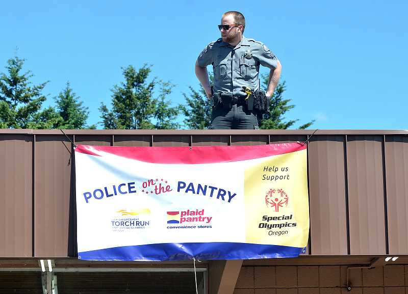 REVIEW PHOTO: VERN UYETAKE - How high will Lake Oswego Community Service Officer Cole Duvall go to raise money for Special Olympics Oregon? On Friday, he climbed to the roof of the Plaid Pantry store on Pilkington Road.