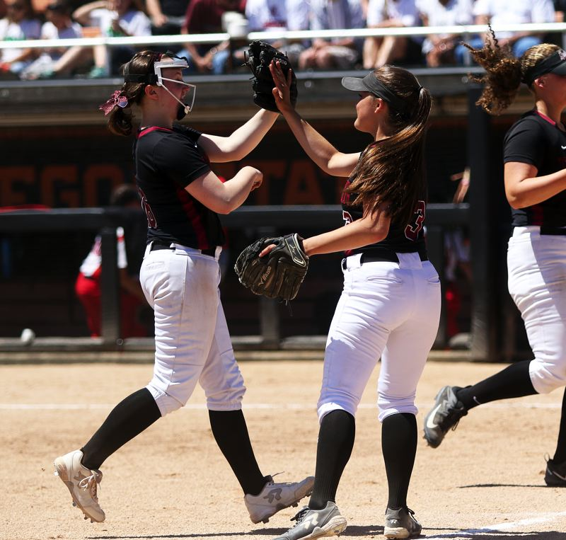 TIMES PHOTO: DAN BROOD - Tualatin seniors Megan Woodward (left) and Taylor Alton celebrate on their way to the dugout.