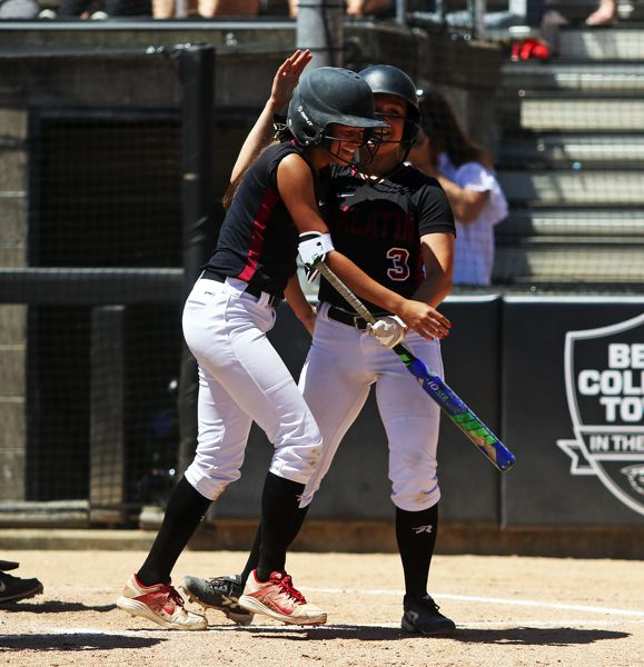 TIMES PHOTO: DAN BROOD - Tualatin sophomore Tia Ridings (left) is congratulated by senior Taylor Alton after scoring a run in Saturday's Class 6A state championship game.
