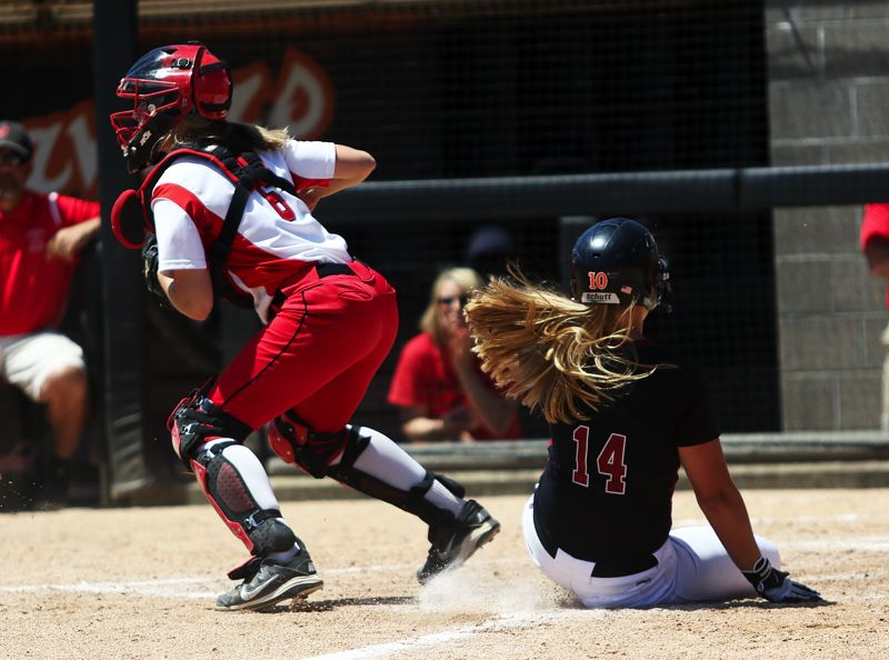 TIMES PHOTO: DAN BROOD - Tualatin freshman Taylor Corcoran (right) is forced out at home plate by Clackamas catcher Kylie Hegar.