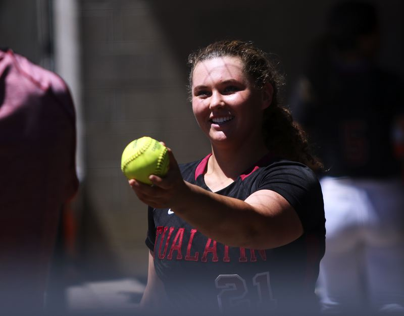 TIMES PHOTO: DAN BROOD - Tualatin junior Emily Johansen hands her home run ball to her father, Mark Johansen, during Saturday's state championship game.