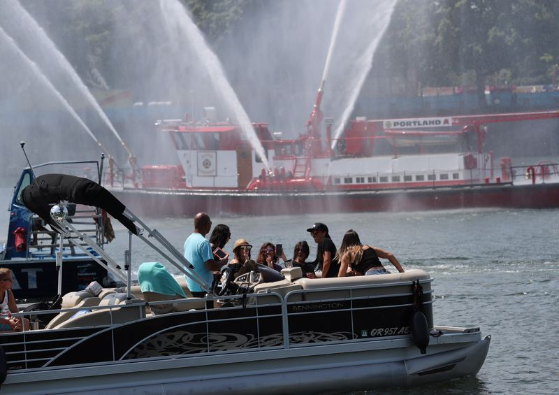 PAMPLIN MEDIA GROUP: JAIME VALDEZ - A private boat stayed outside of spray range while watching the arriving Rose Festival Fleet Wednesday afternoon, June 6, on the Willamette River.