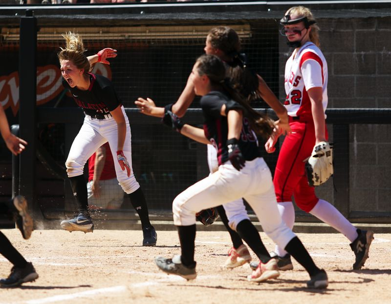 TIMES PHOTO: DAN BROOD - Tualatin senior Ella Hillier (left), after scoring the winning run, looks to join her teammates in running out to celebrate with freshman Tayor Corcoran.