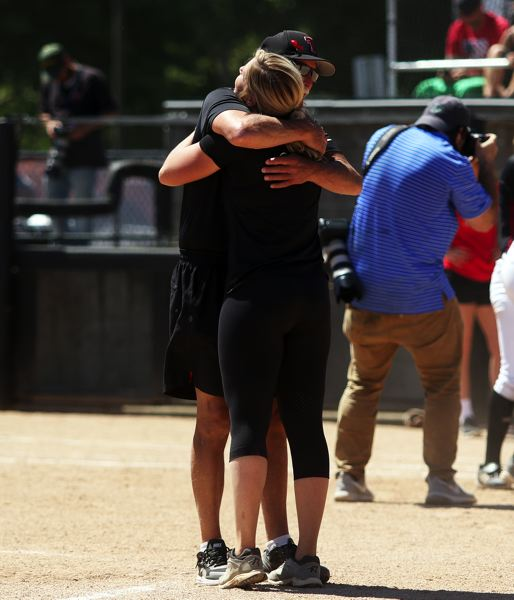TIMES PHOTO: DAN BROOD - Tualatin head coach Jenna Wilson hugs her father, and assistant coach, Bill Wilson following the Wolves' 4-3 win in Saturday's state championship game.