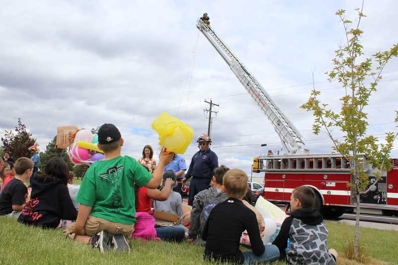 HOLLY M. GILL - Jefferson County Fire Department personnel gather up eggs from third-grade students at Buff Elementary on May 31, for the annual egg drop. Volunteer Onasis Adame waits on top of the ladder for the eggs.