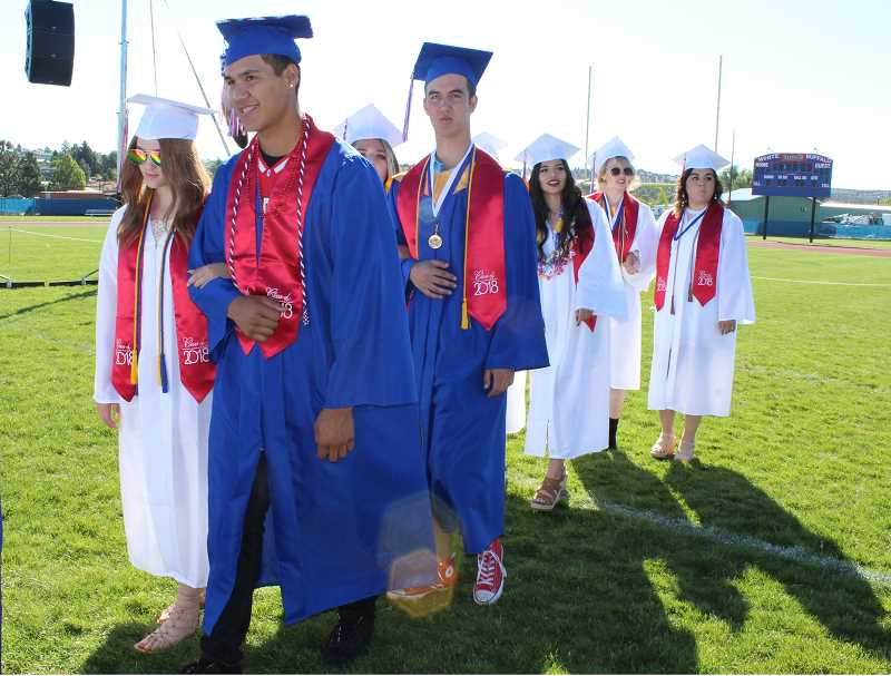 HOLLY M. GILL/MADRAS PIONEER - Maadras High School seniors, from left to right, Riley Flowers and Kanim Smith, Kelsey Harmon and Kyle Hartman, Meleah Clements, Jacey Kelly and Gabby Nambo file in on graduation day, June 2, at Madras High School.