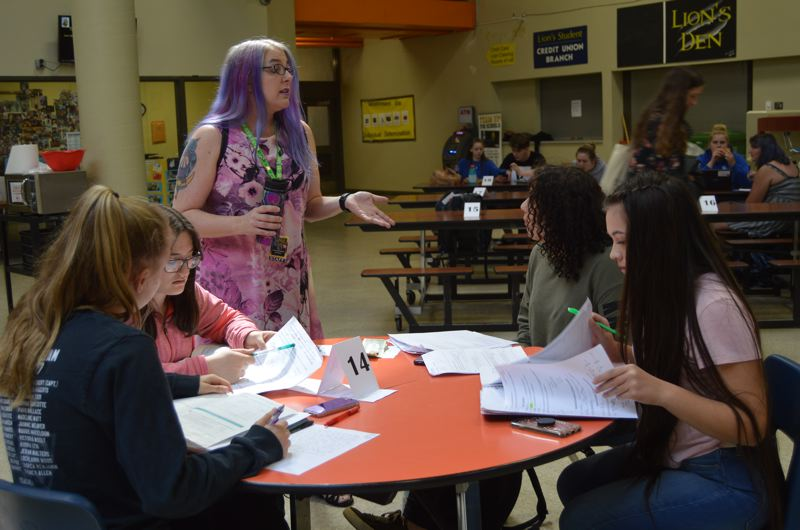 SPOTLIGHT PHOTO: NICOLE THILL - Awen Moon Gatten, center, speaks with a group of students at St. Helens High School during a Cocoa and Cram study session on Tuesday, June 5. Gatten works as a mentor and tutor at the high school and will be a student speaker at the Portland Community College graduation next week.