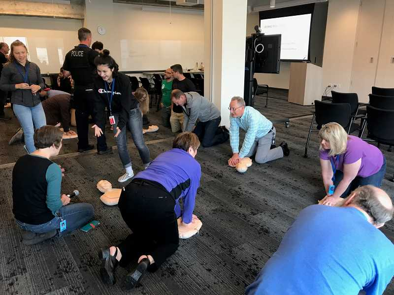 SUBMITTED PHOTO: JAMIE INGLIS  - Employees of a Portland company receive Hands-Only CPR training from Lakeridge High students and Lake Oswego police officers during a June 1 clinic. Although brief, the training is an integral part of first-response efforts in a 'moment's-notice' situation.