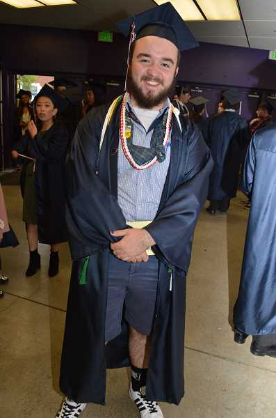 TIMES PHOTO: RAY PITZ - Mason Kennedy pauses for a quick photo before marching out to the Chiles Center main floor for graduation. Kennedy said he was the only person he had seen so far Thursday evening wearing shorts beneath his gown.