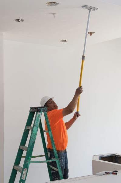 STAFF PHOTO: CHRISTOPHER OERTELL - A worker sands down a primer coat on the ceiling of what will be the Pink Spoon frozen yogurt shop at Forest Grove's Stonewood Center.