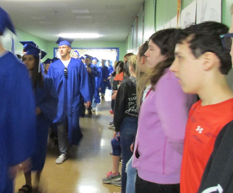 OUTLOOK PHOTO: TERESA CARSON - Hopefully Dexter McCarty Middle School students will be inspired to graduate after watching the big kids from Gresham High walk through the school in their caps and gowns.