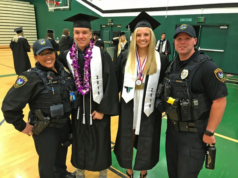TIMES PHOTO: DANA HAYNES - School resource officers Kristan Rinell and Brian Imus flank graduating seniors Cole Green and Lauren Paven.