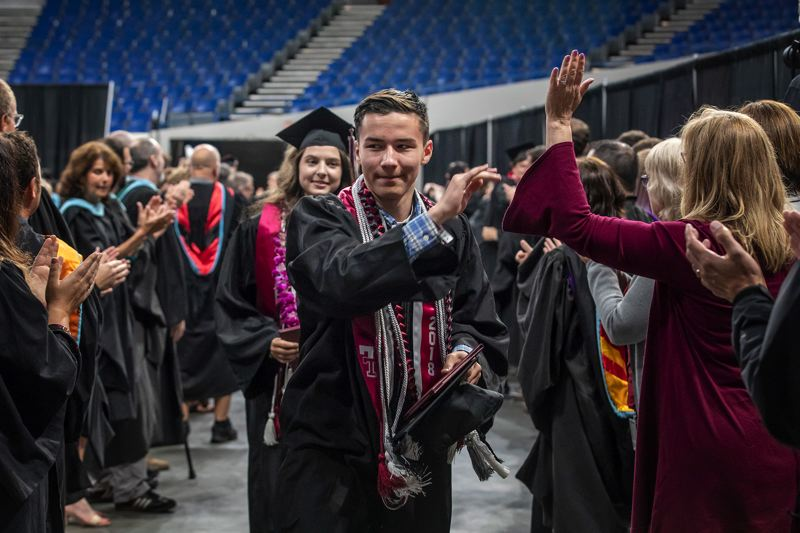 """TIMES PHOTO: JONATHAN HOUSE - Coleman Kotchik leads the procession of newly-minted Tualatin graduates through the """"gauntlet"""" of faculty and out of Memorial Coliseum."""