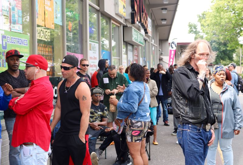 TRIBUNE PHOTO: ZANE SPARLING - Frank Whitesell (far right) smokes a cigarette while waiting in line for Legal Services Day on Friday, June 8. The line for help stretched past the Su Casa Super Mercado.