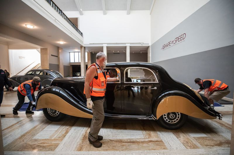 PHOTO BY JONATHAN HOUSE - Workers push the 1939 Panhard & Levassor type X81 Dynamic sedan into its spot at the art museum.