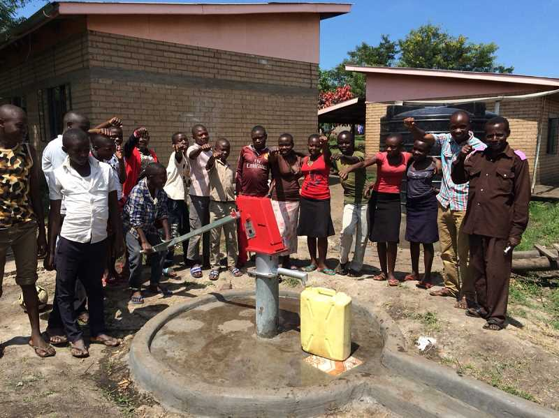 COURTESY PHOTO - Students at Mpondwe Lhubiriha Secondary School gather to collect water at their school's new well, which was paid for by the fundraising efforts of West Union sixth-grader Crawford Sly.
