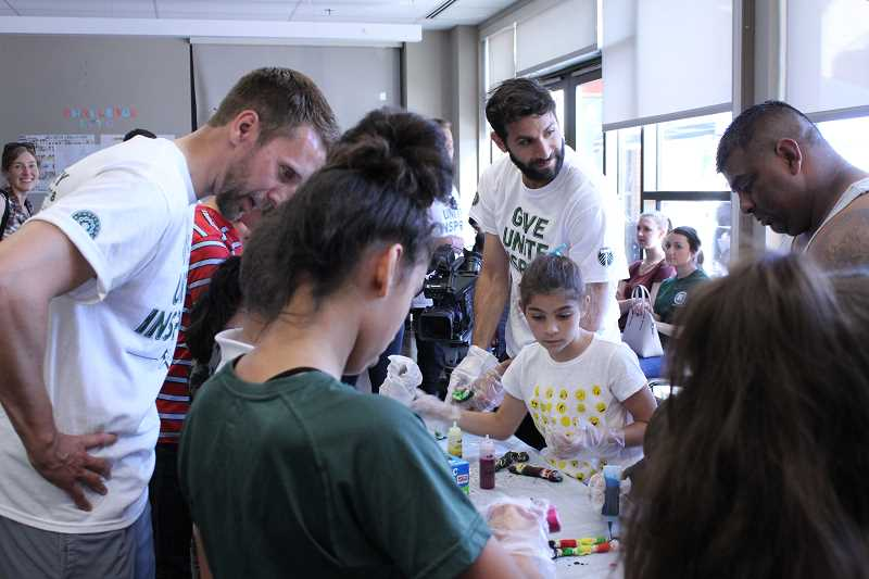STAFF PHOTO: HOLLY BARTHOLOMEW - Portland Timbers players help kids at an activity table at Virginia Garcia Memorial Health Center in Cornelius on Monday, June 11.