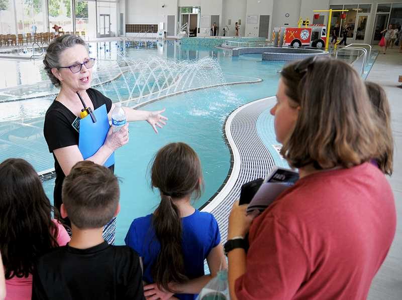 SETH GORDON -  Aquatic coordinator Tara Franks gives a tour of the leisure pool. A massive front desk can easily accommodate patrons at the aquatic center.