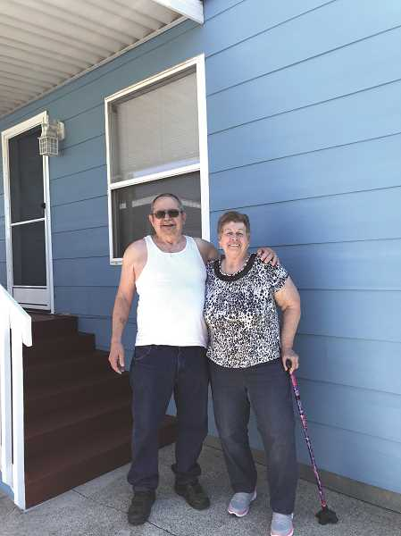 COURTESY PHOTO: BLANCA GUTIERREZ - Wanda and Robert Girard stand outside their newly-painted home. The exterior paint job was donated by Woodburn company JB Coloringbrush Painting LLC through its Paint It Forward giveaway.