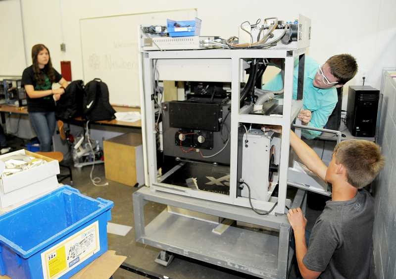 SETH GORDON - Newberg High School students Christian Evans (at right) and Paul Sperling (at right below) work to remove the case from a 3-D printer that was donated to the Robotics program. Students recently completed renovations to its lab within the NHS machine shop that will increase usability and appeal to younger students.