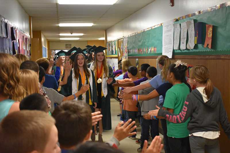 ESTACADA NEWS PHOTO: EMILY LINDSTRAND - Graduating Estacada High School seniors receive high fives from River Mill Elementary Students during the annual grad walk on Friday, June 8.